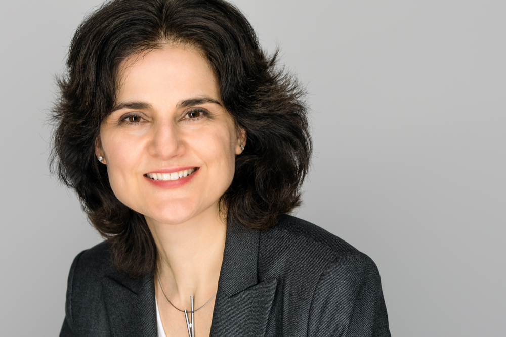 Professional headshot of Lia Chiarotto with grey background